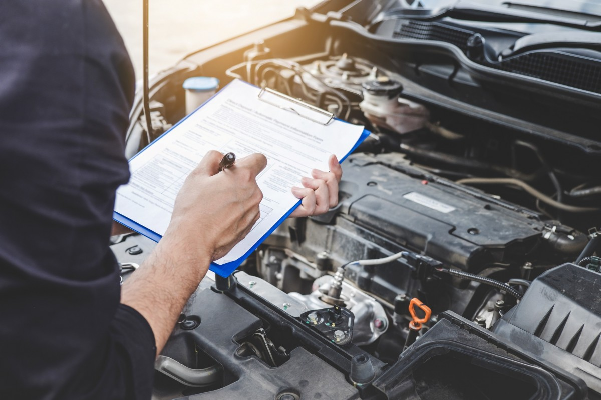 Mechanic holding checklist while checking on vehicle repairs