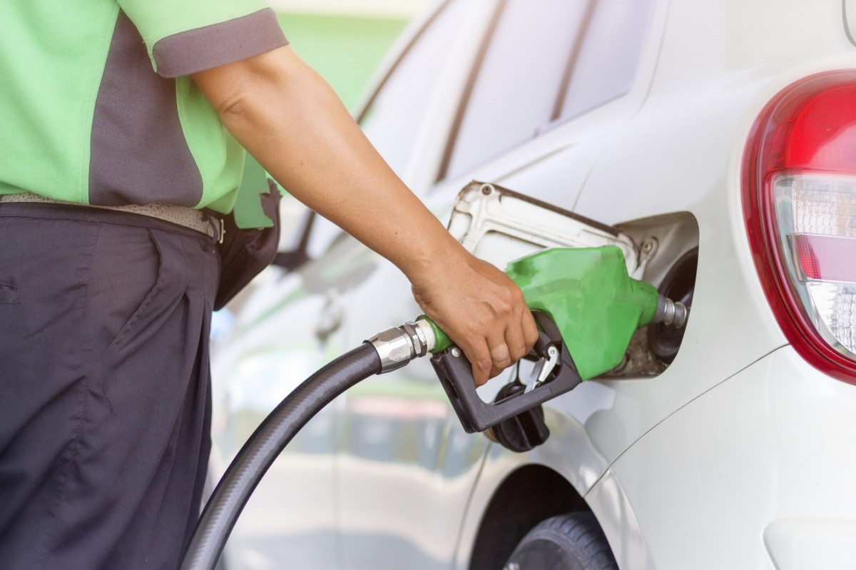 man putting gas in a vehicle at the pump
